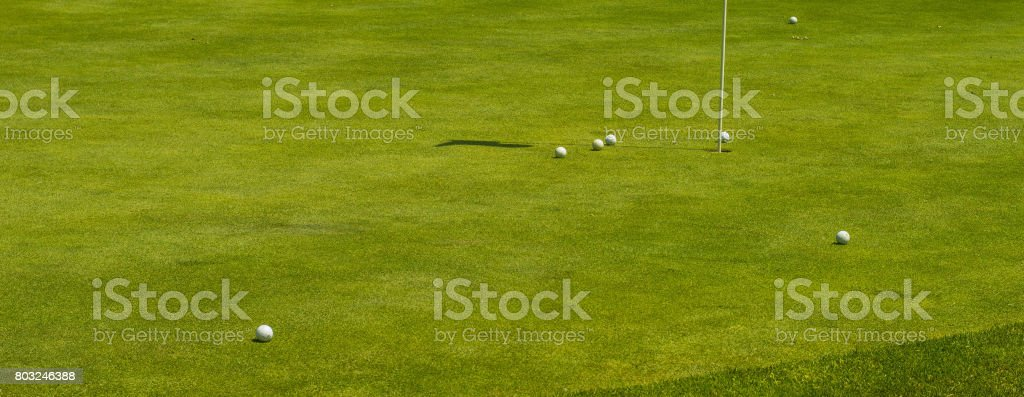 Green golf court full of golf balls gathering around single white flag and hole on a sunny bright day stock photo