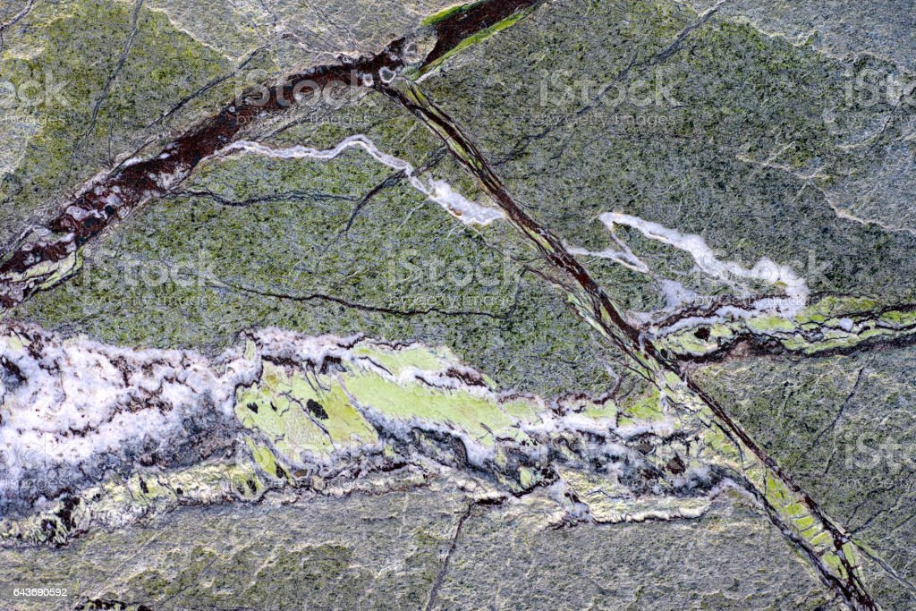 Green granite stone background with dark red lines stock photo