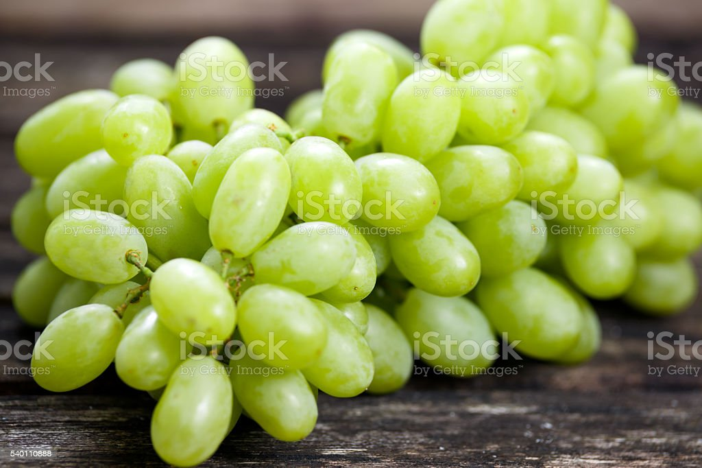Green grape, close up  on old wooden table. background. selected stock photo