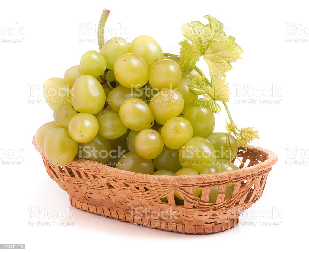 green grapes in a wicker basket isolated on white background stock photo