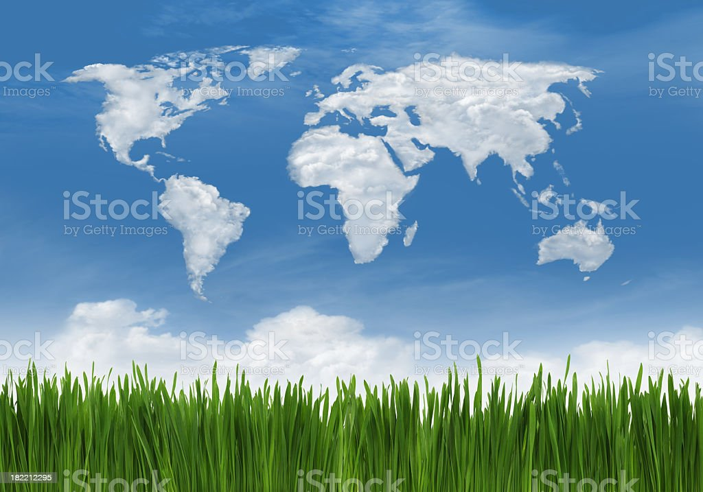 Green grass against sky with world outline in clouds stock photo