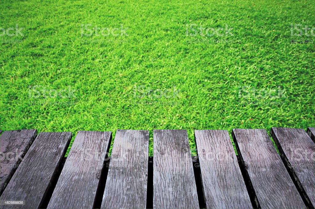 Green grass blurred background and old brown wooden floor. royalty-free stock photo