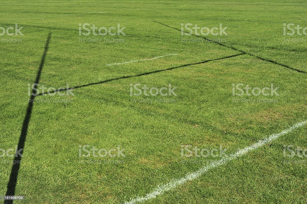 Green grass of a rugby field with shadow of a goalpost stock photo