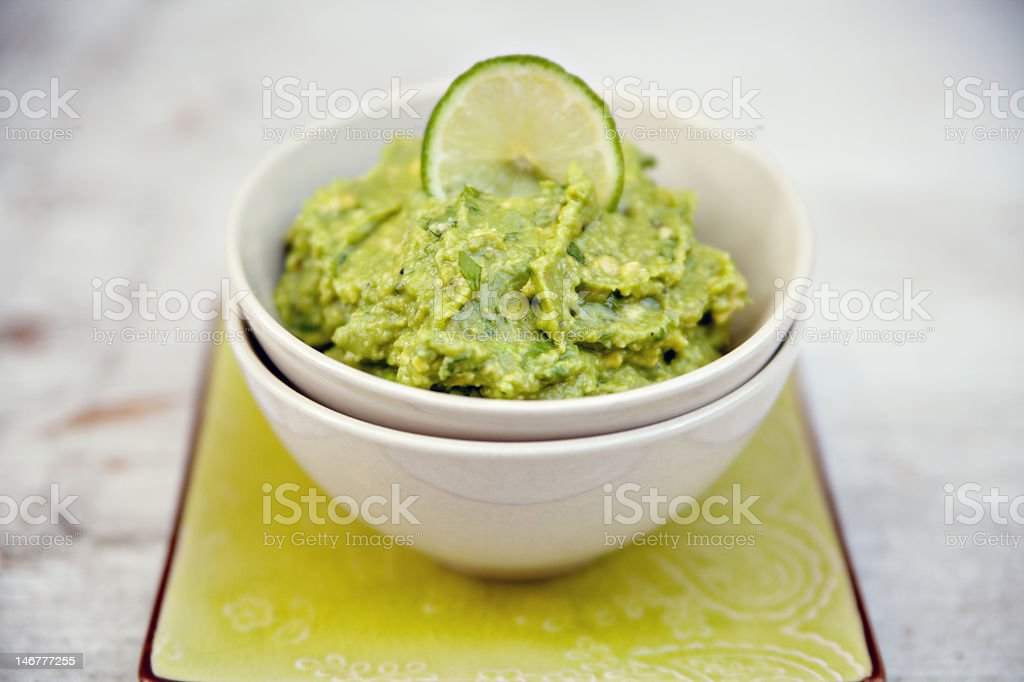 Green guacamole in a white bowl royalty-free stock photo