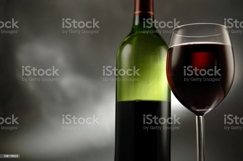 Green half-full bottle of red wine with full glass beside it royalty-free stock photo
