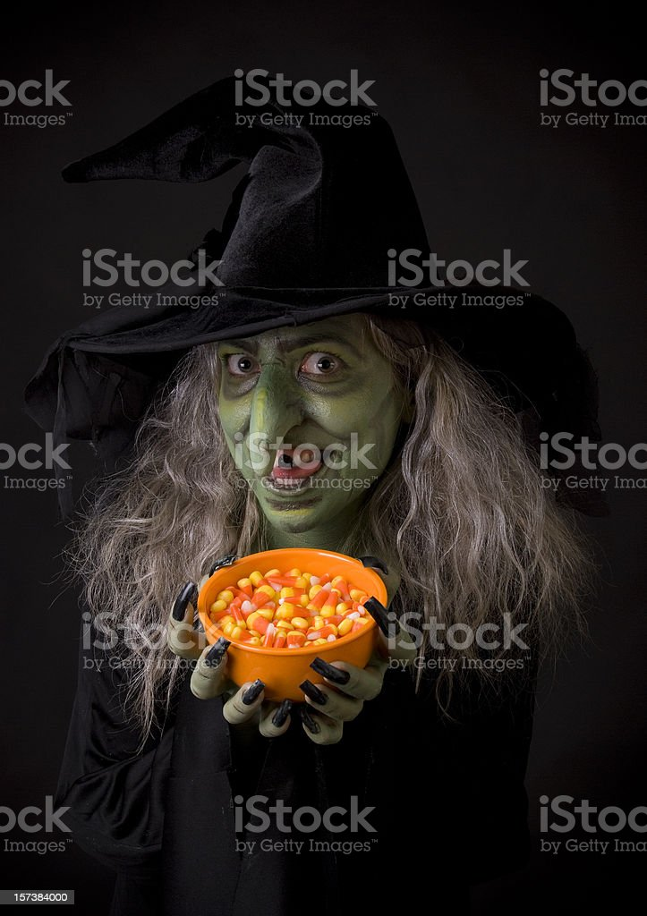 Green Halloween witch holding orange bowl of candy corn stock photo