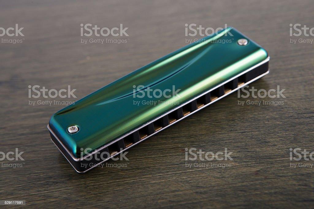 green harmonica on wooden board stock photo
