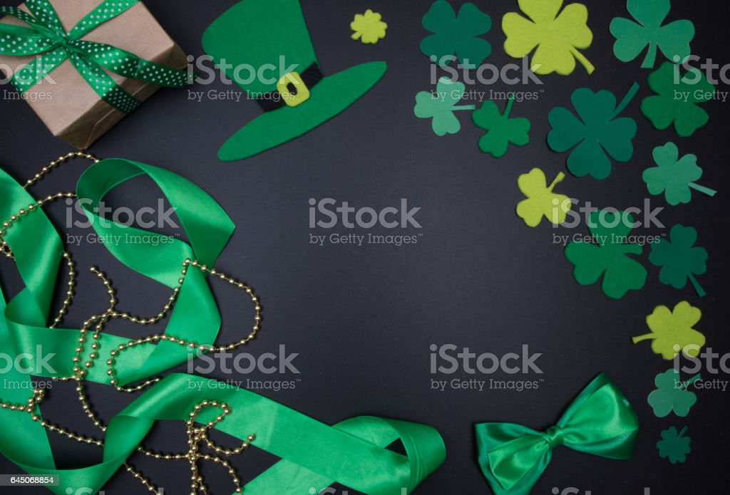 Green hat and shamrocks Quarterfoil on blackboard. St.Patrick s Day stock photo