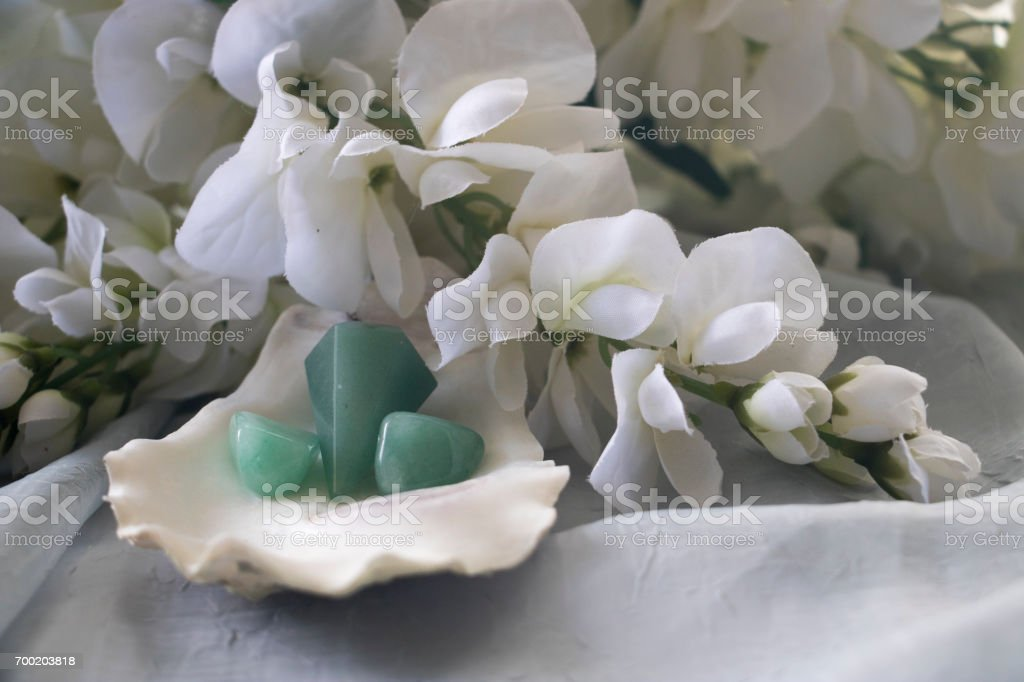 A green heart pendant and two green aventurine crystals in a seashell surrounded by white flowers. stock photo