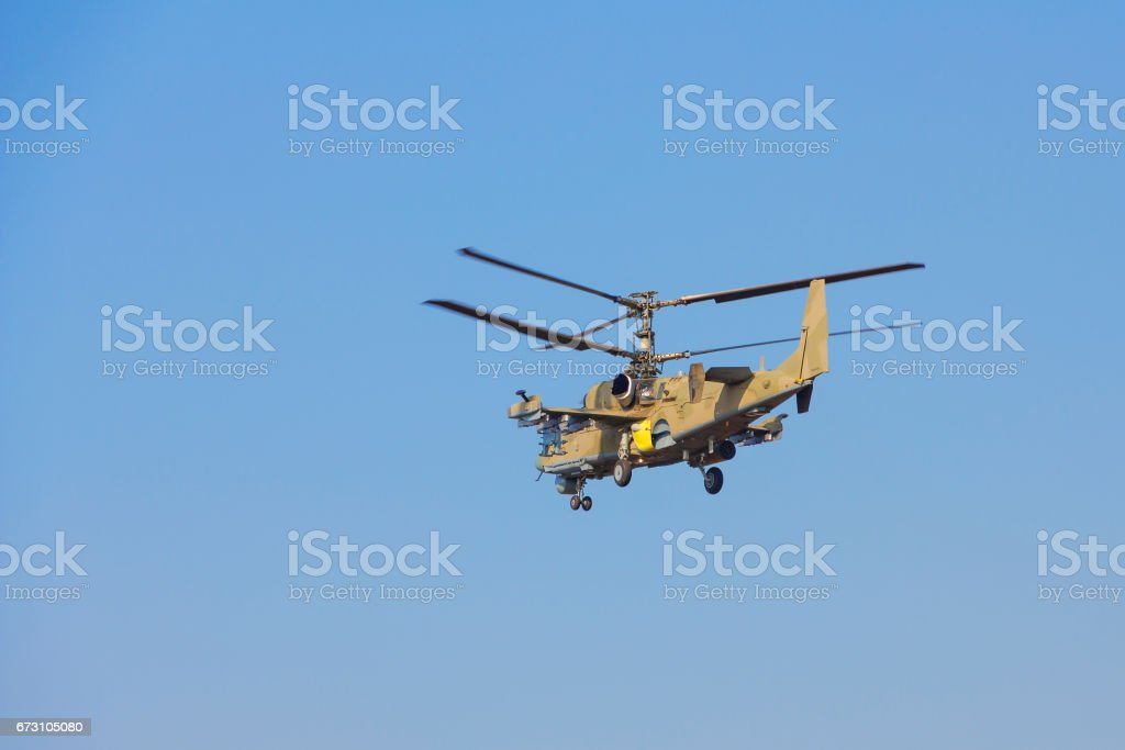 Green helicopter flies against the blue sky stock photo