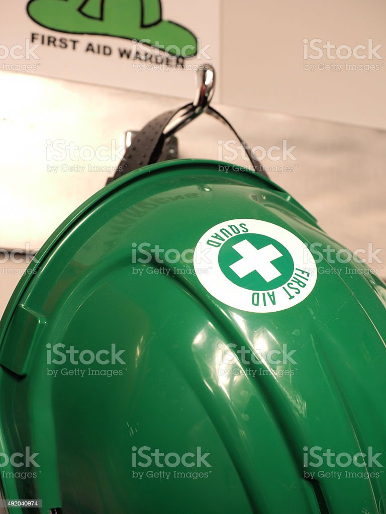 Green helmet of a first aid practitioner on a wall stock photo