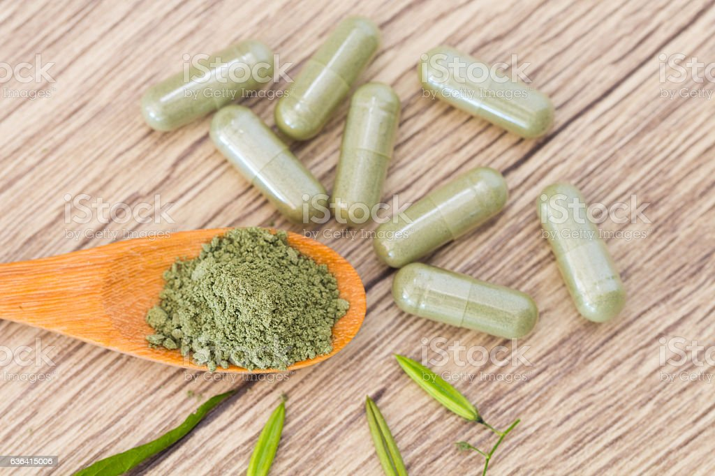 Green herb powder capsules and erlenmeyer flask stock photo