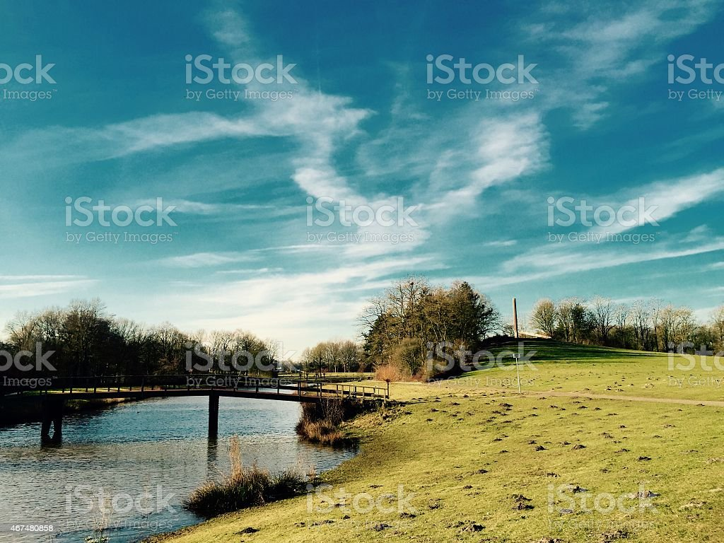 Green hill in a park with a pond in Enschede stock photo