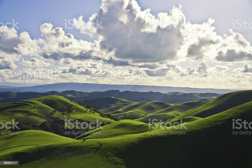Green hills and cloudy sky view stock photo