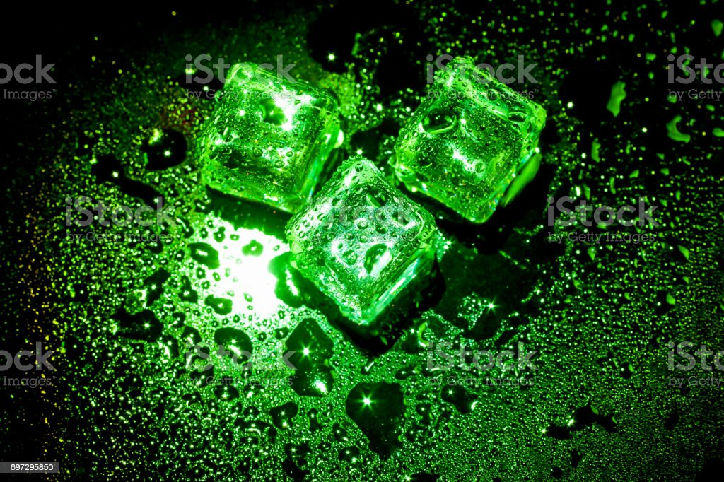 Green ice cubes on black wet table. stock photo