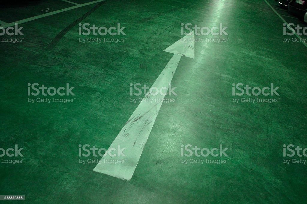 Green illuminated arrow symbol on concrete floor stock photo