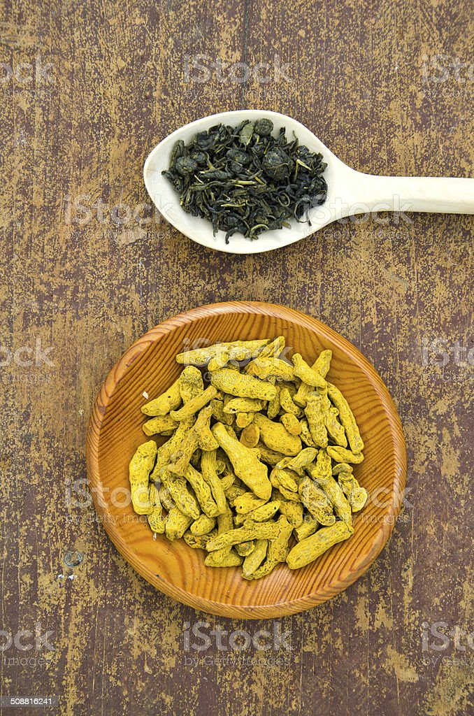 green indian tea and dry turmeric root in wooden plate stock photo