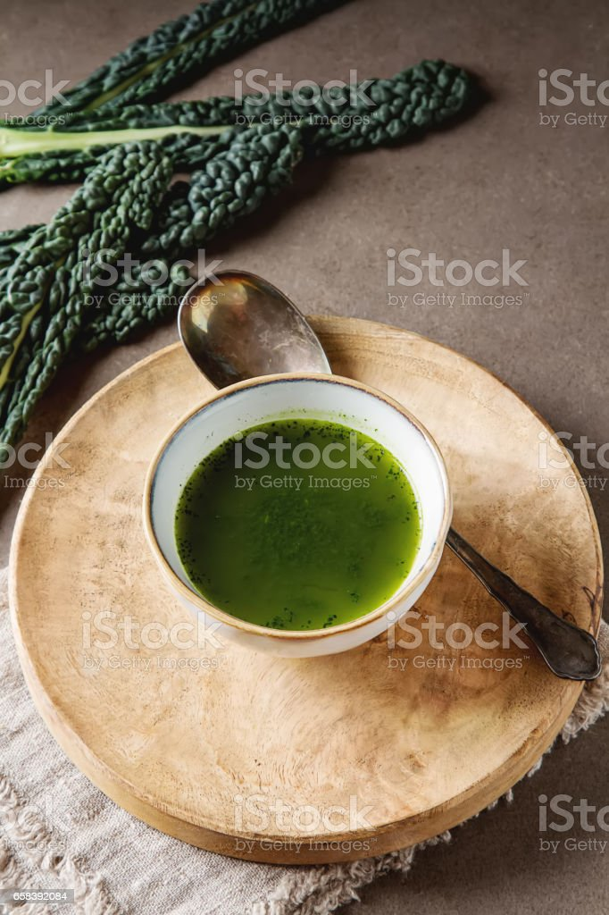 Green Italian soup made from cabbage kale in a white plate. Dark stock photo