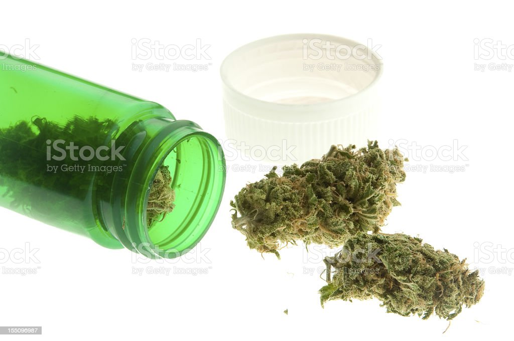 A green jar of marijuana spilled on its side royalty-free stock photo