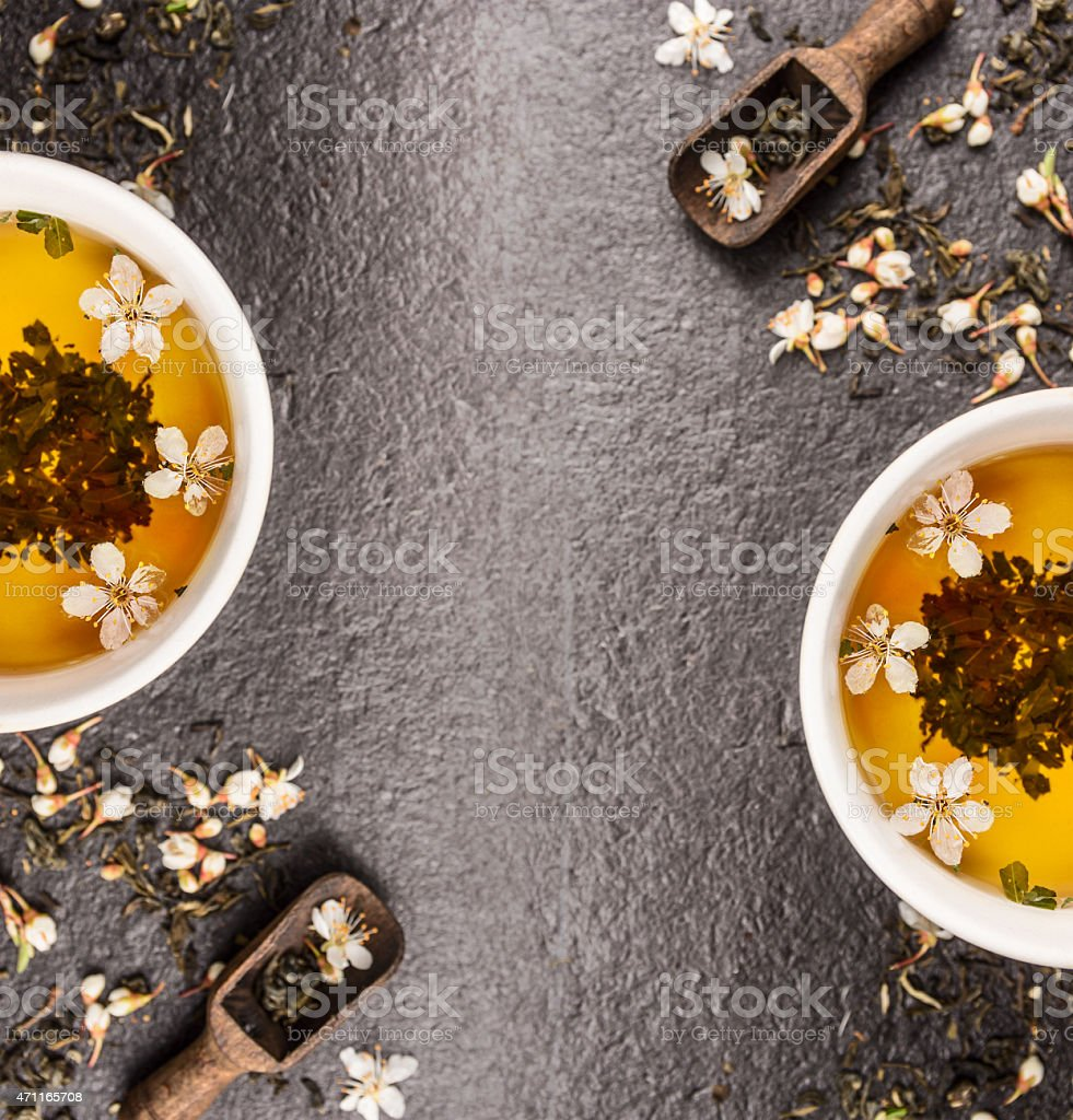 Green Jasmine tea with fresh flowers and  cups stock photo