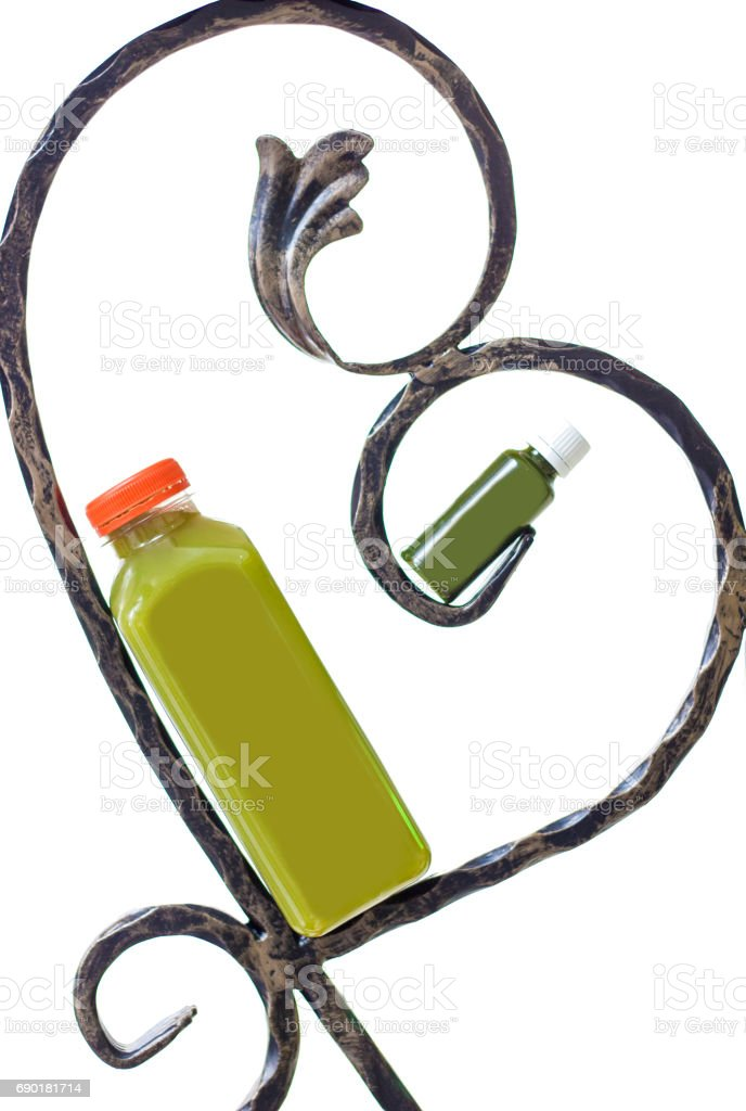 Green juice in bottle leaning on iron hearth frame, small and big stock photo