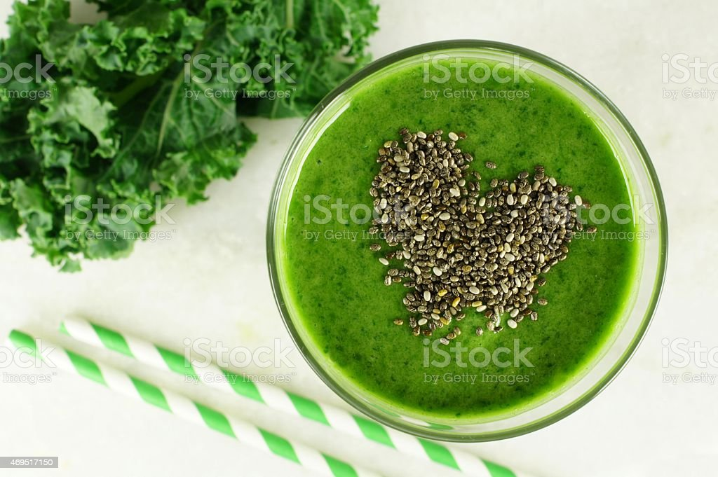 Green kale smoothie with chia seeds heart stock photo