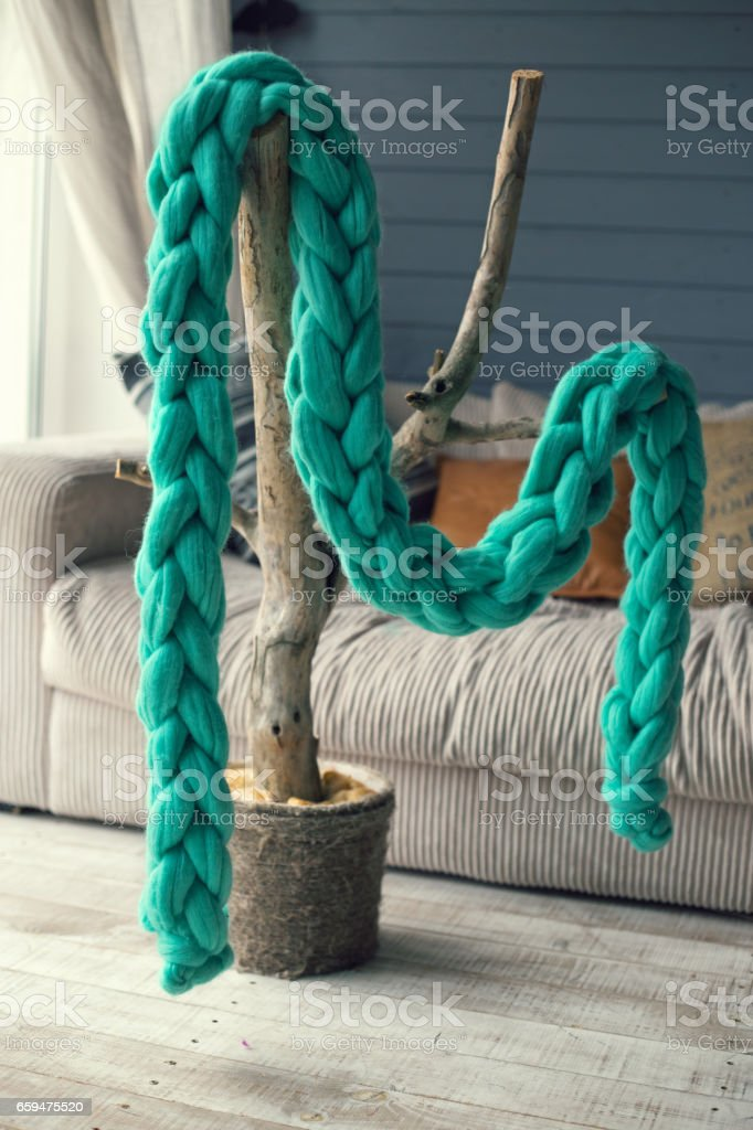 Green knitted scarf of merino wool hangs on an artificial tree in casual interior stock photo