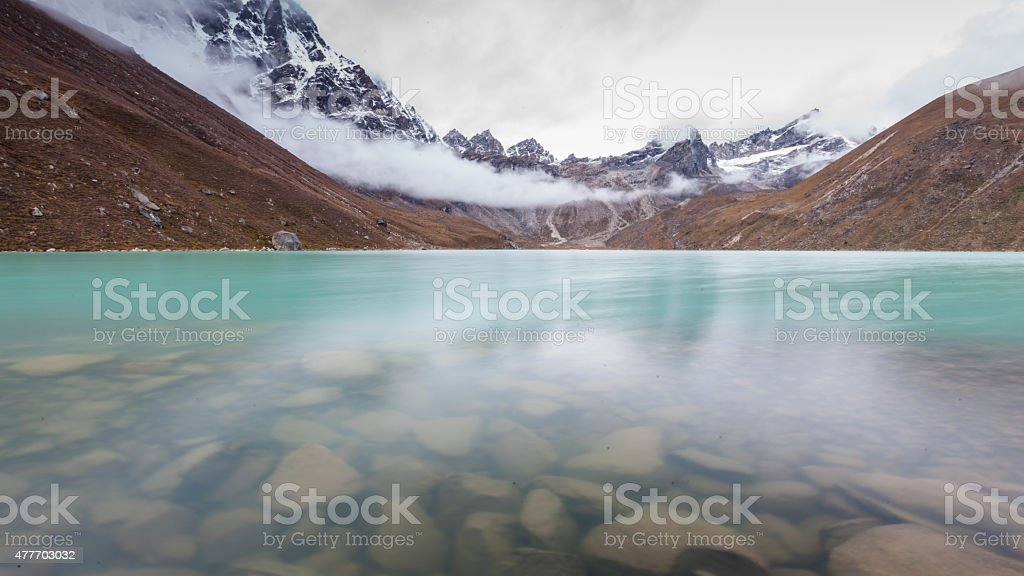 Green lake between mountains in cloudy day stock photo