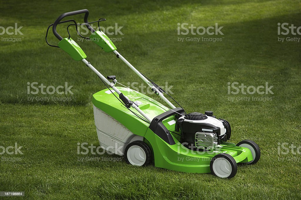 Green lawnmower on the lawn royalty-free stock photo