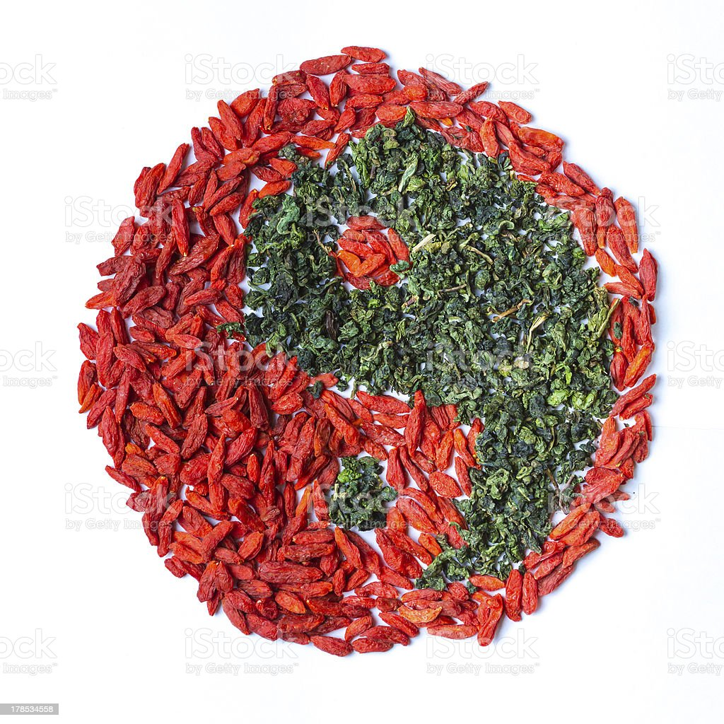 Green leaf tea versus cgoji berries in Yin Yang shape royalty-free stock photo