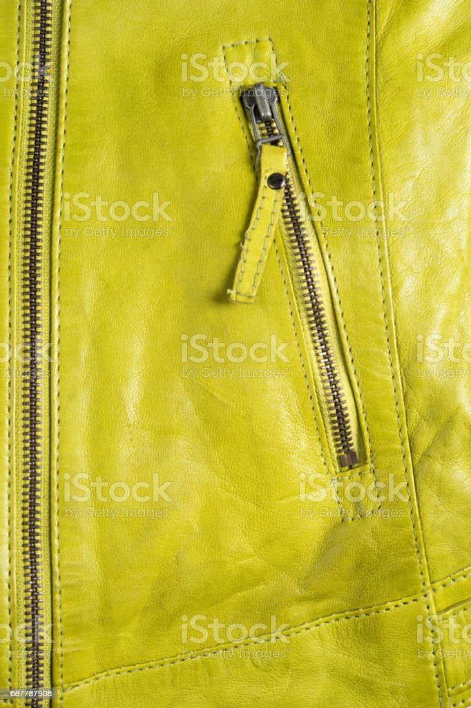 Green leather jacket zippers. Leather jacket macro details. Jacket zippers and pockets stock photo