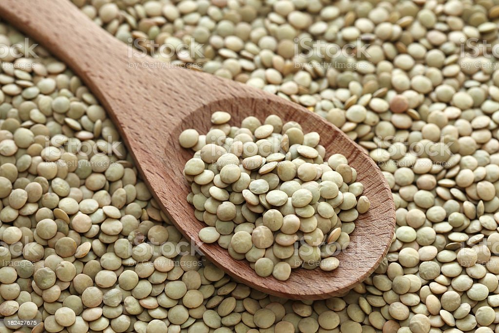 Green lentils in a wooden spoon stock photo