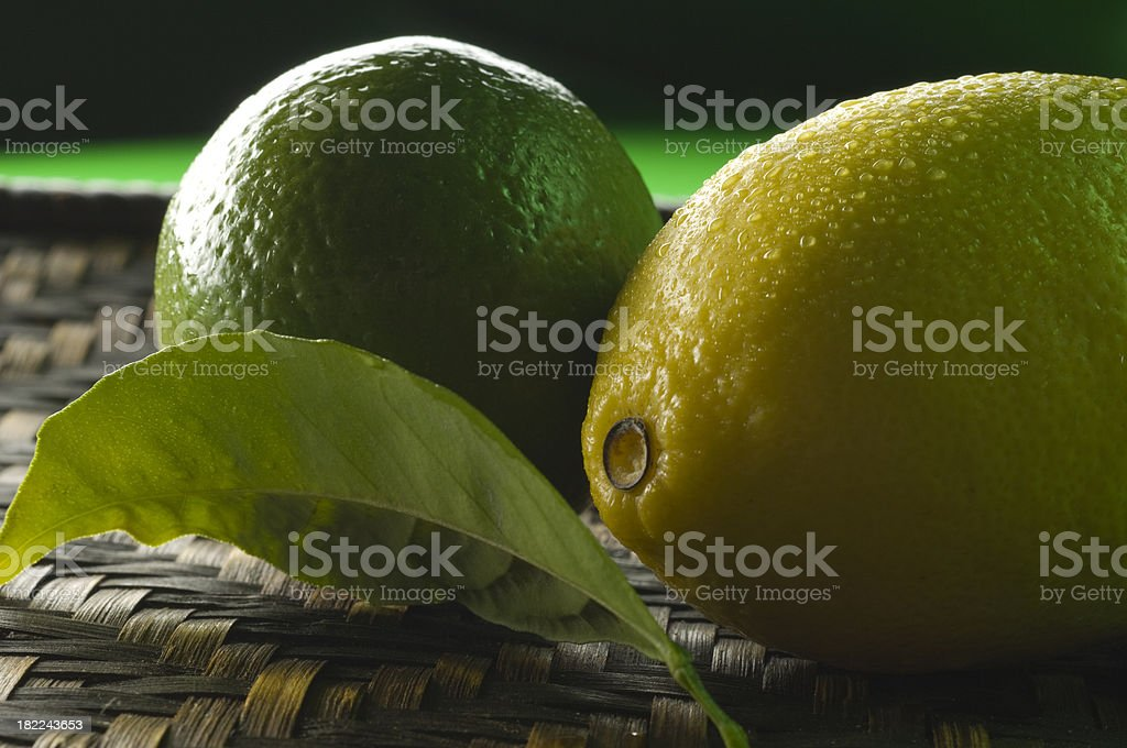 Green lime and lemon with citrus leaf on the mat. royalty-free stock photo