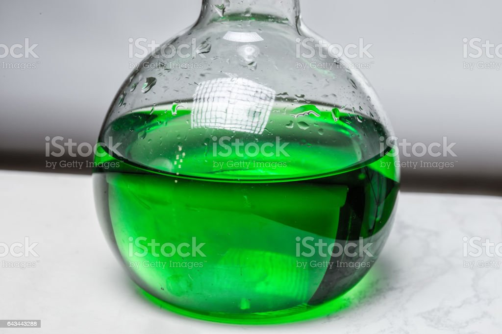 Green liquid in glass flask stock photo
