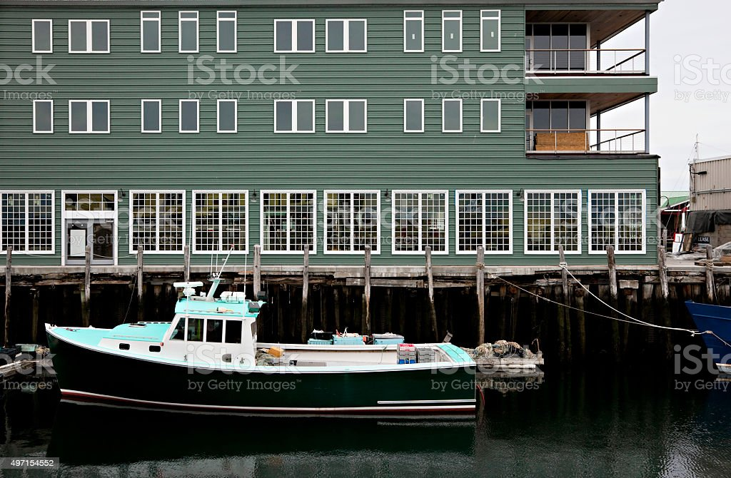 Green lobster boat in front of green shipyard building stock photo