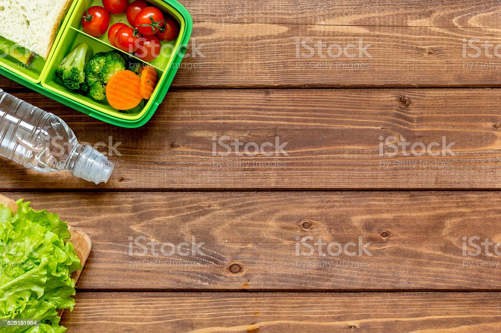 green lunch box for kid on wooden background top view stock photo