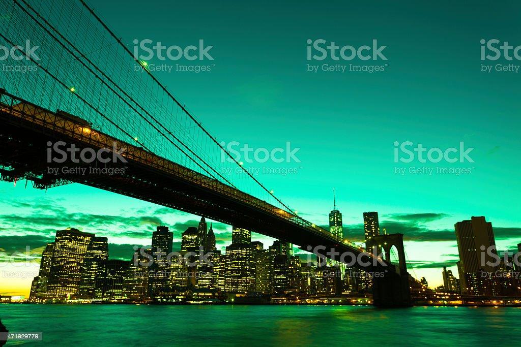 Green Manhattan Skyline with Brooklyn Bridge at Sunset stock photo