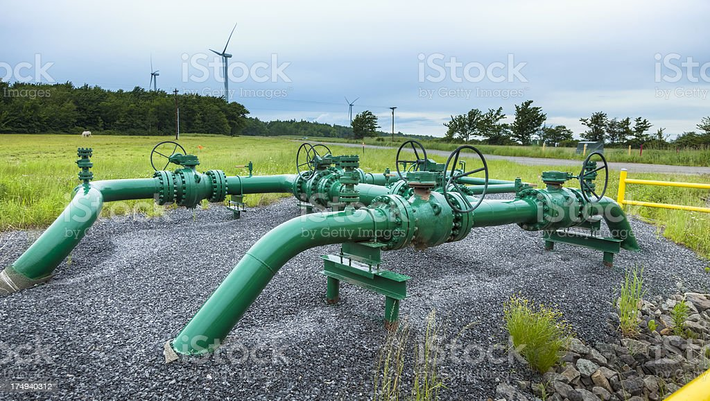 Green Marcellus shale gas pipelines in grass field stock photo