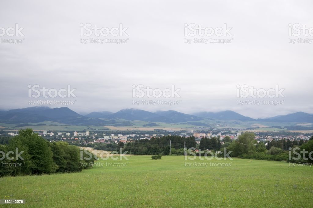 Green meadow and hills during sunny and cloudy afternoon. stock photo