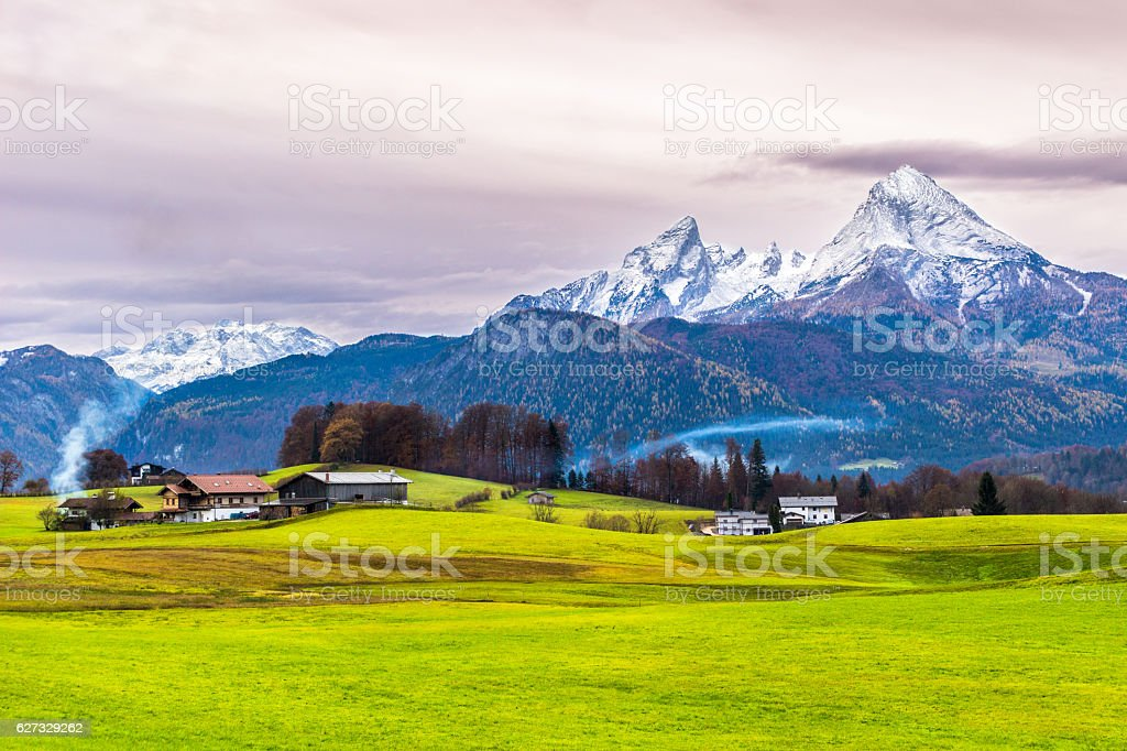 Green meadow, farmer houses and  snow-capped Watzmann mountain. Germany. stock photo