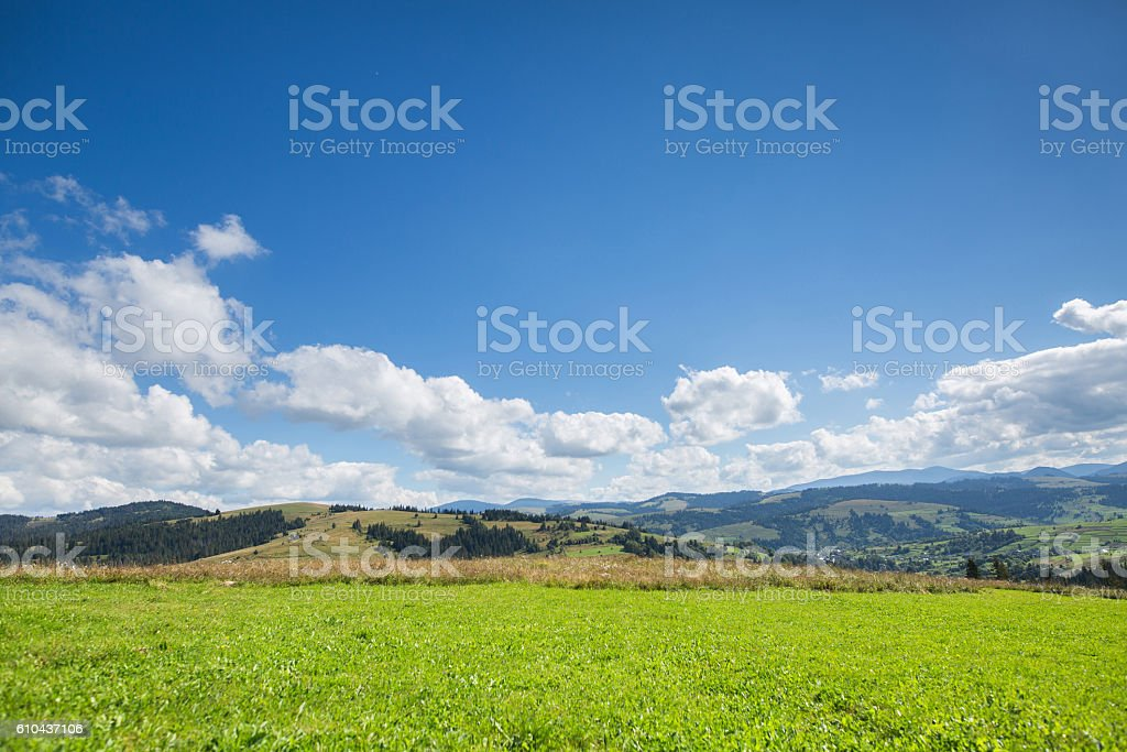 Green meadow, mountain and sky with clouds stock photo