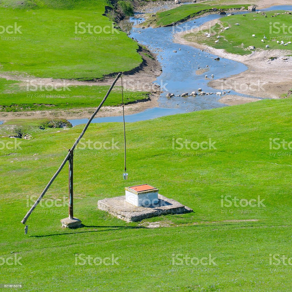 Green meadow, river and well Crane stock photo
