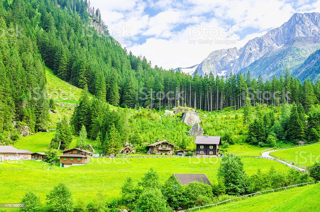 Green meadows, alpine cottages and mountain peaks stock photo