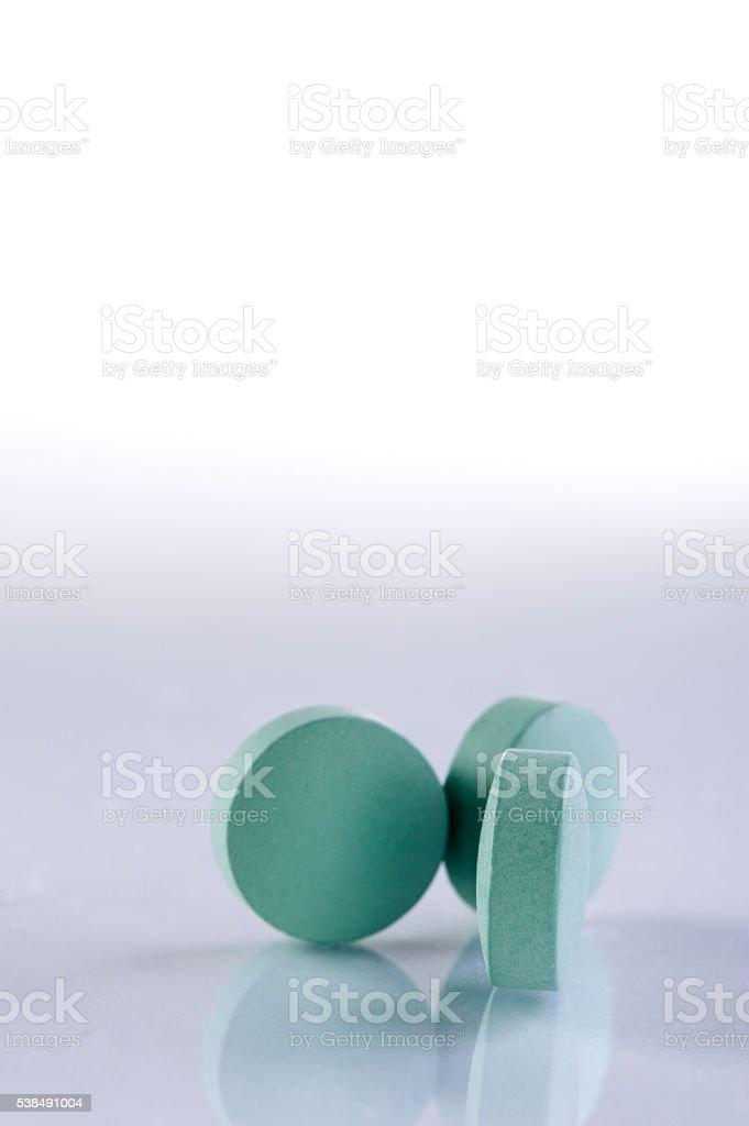 Green medicine pills on white background. stock photo