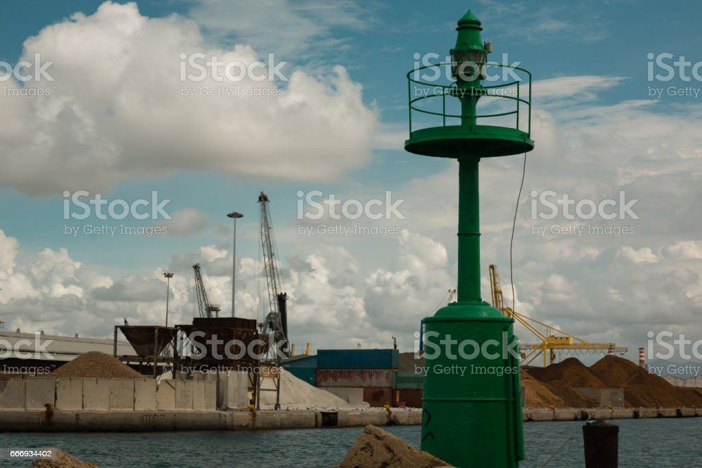 Green Metallic Lighthouse, Blue Sky with Clouds and Shipyard in Background stock photo