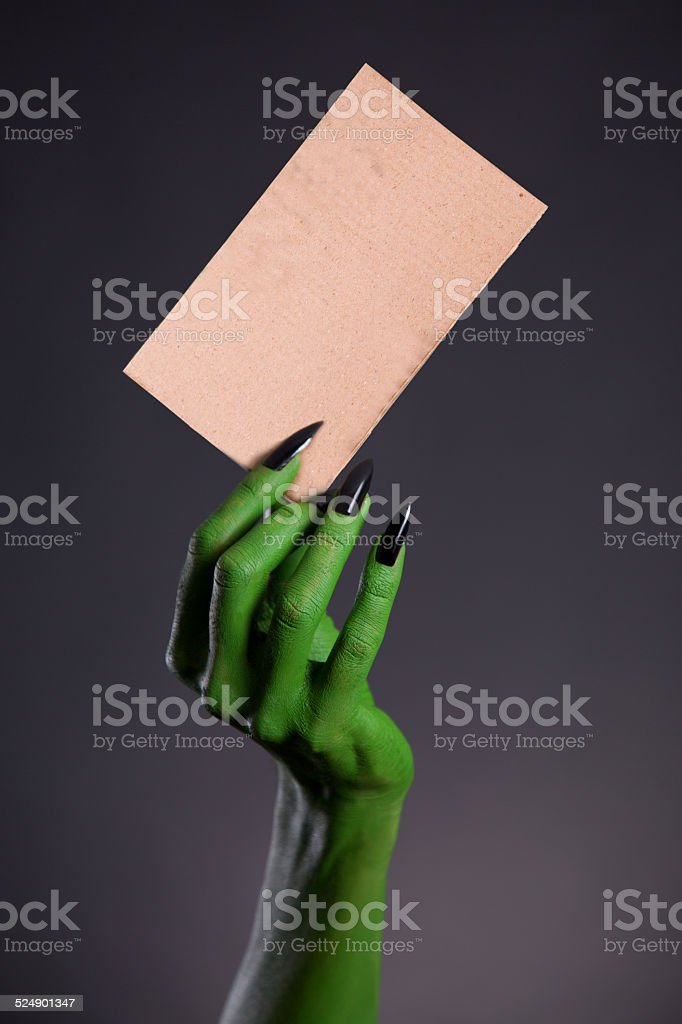 Green monster hand holding blank piece of cardboard stock photo