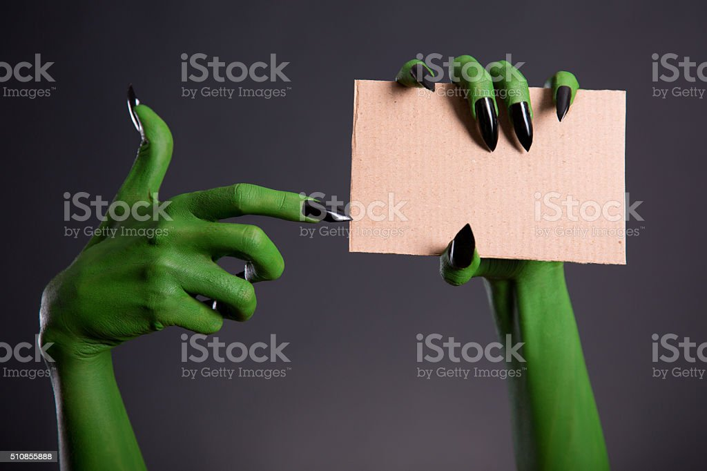 Green monster hand with black nails stock photo