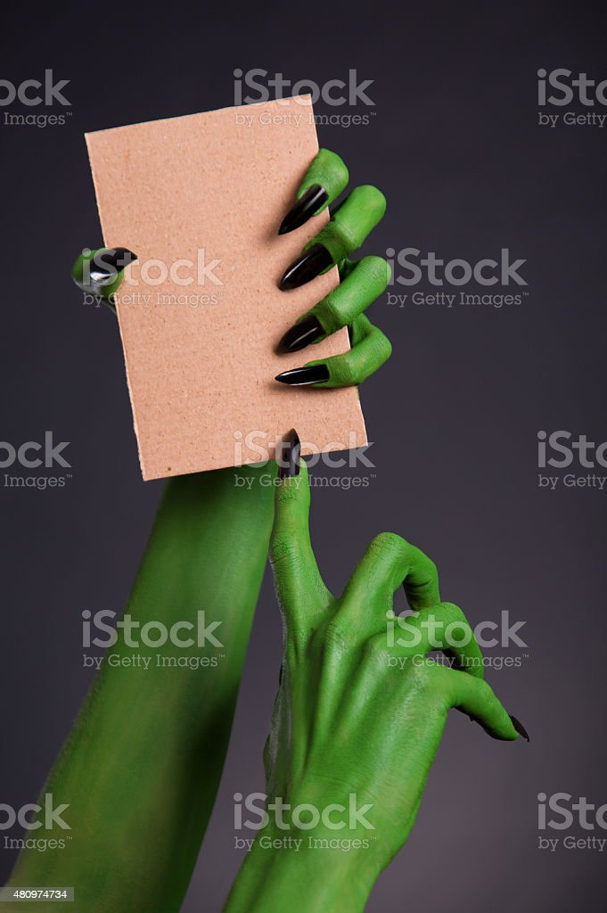 Green monster hands holding blank piece of cardboard stock photo