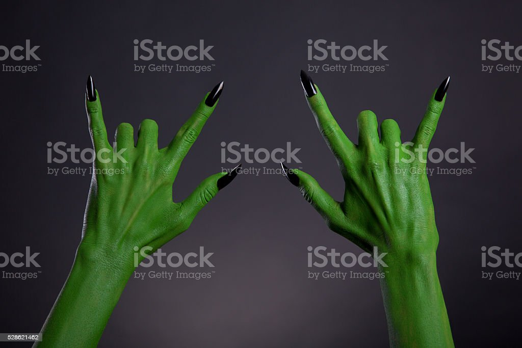 Green monster hands with black nails showing heavy metal gesture stock photo