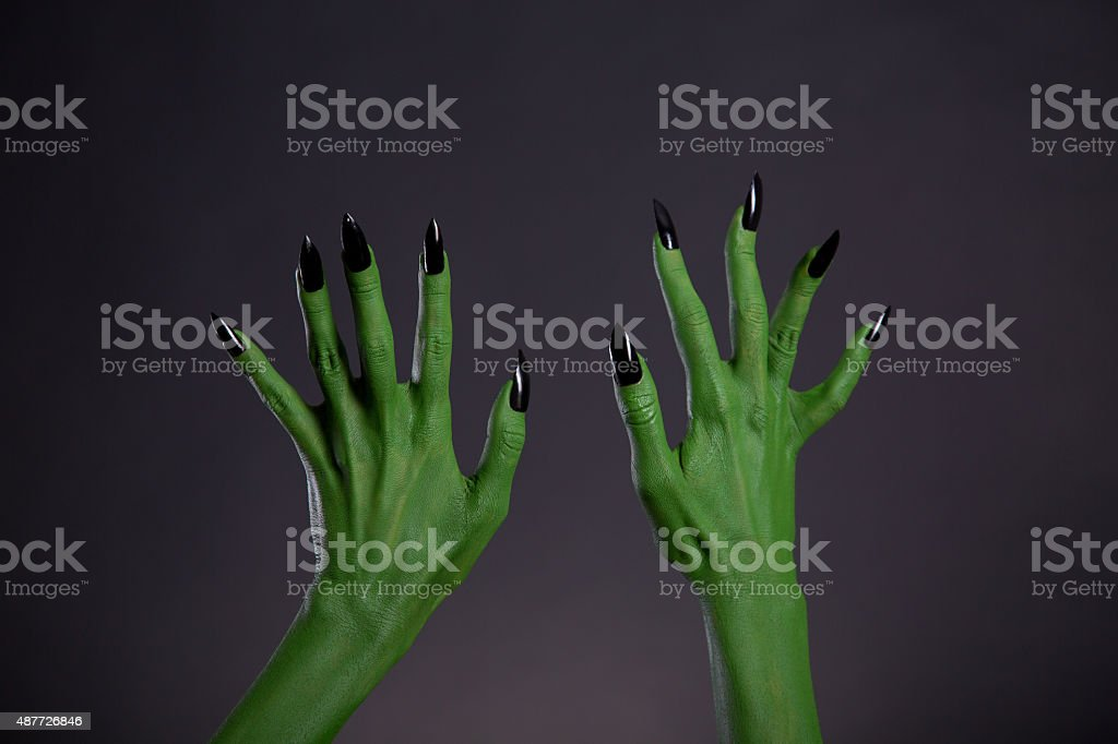 Green monster hands with sharp black nails, body-art stock photo
